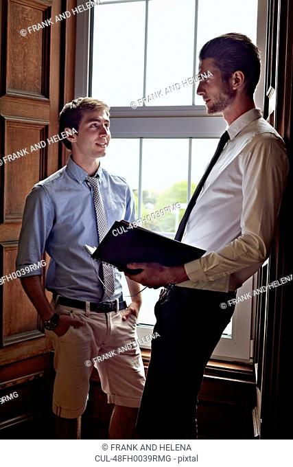 Businessmen talking by window
