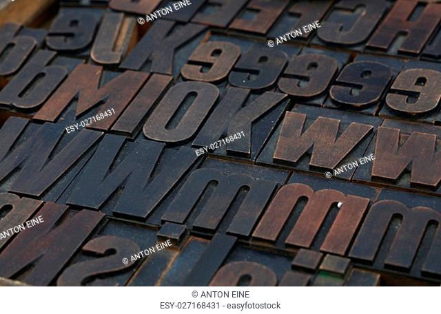 Old dark wooden vintage antique offset typography letterpress printing blocks grunge dirty with paint, mixed alphabet, close up, high angle view