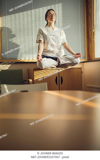Female doctor meditating by window