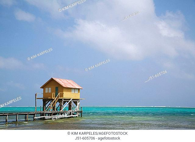 BELIZE San Pedro on Ambergris Caye   Colorful wooden building on stilts, end of dock, Caribbean waters