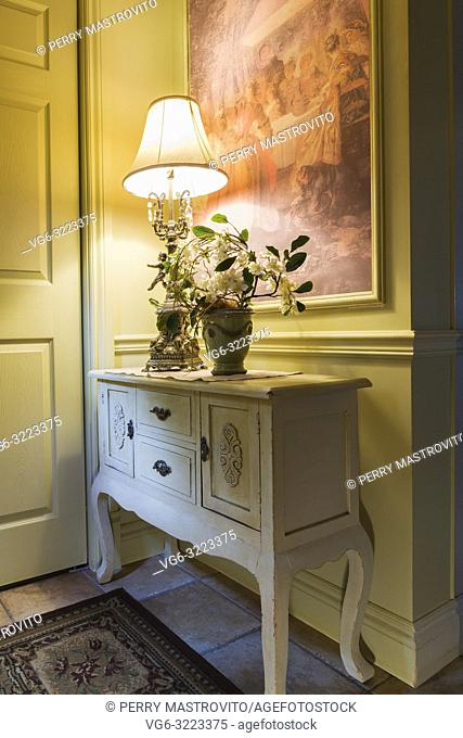 Antique wooden console with lamp and flower vase in the kitchen entryway inside a 2006 reproduction of a 16th century Renaissance castle style residential home