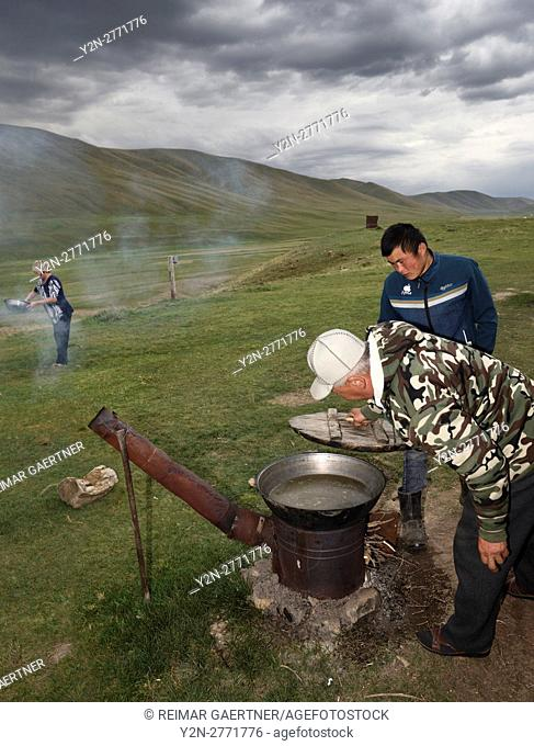 Kazakh family stewing meat on an outdoor oven on summer pasturelands of Assy Plateau Kazakhstan