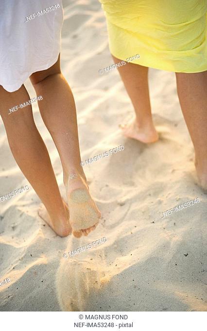 Scandinavian mother and daughter walking on a beach