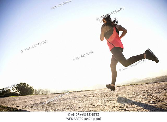 Young woman running in sunlight