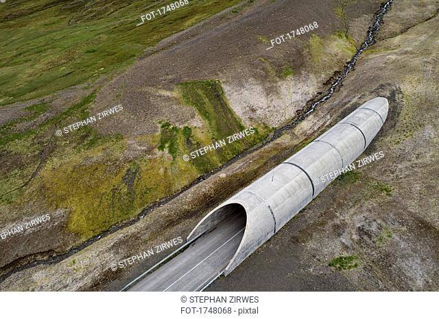 Drone view of tunnel through landscape, Iceland