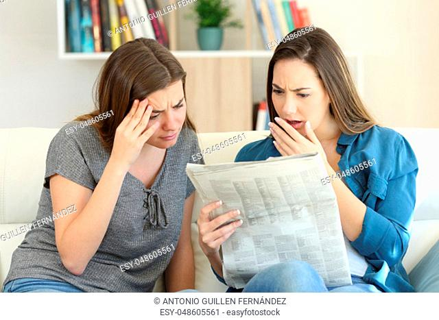 Worried friends reading newspaper news sitting on a couch in the living room at home