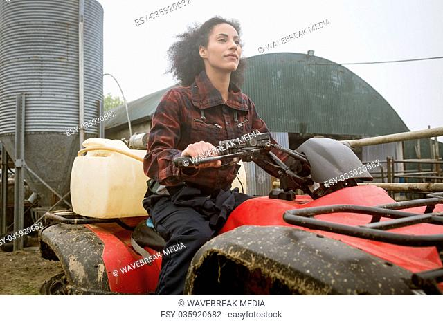 Beautiful female farmer driving vehicle