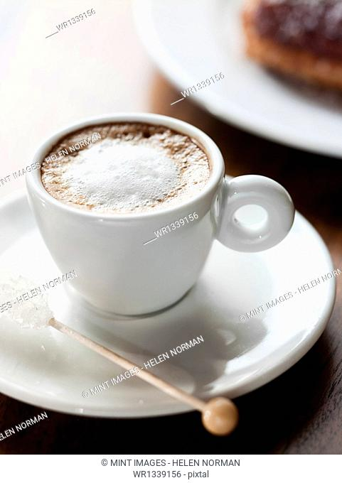 A cup of coffee in a white china cup. Frothy coffee drink