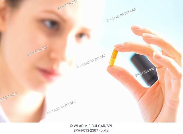 Woman holding a capsule, close up