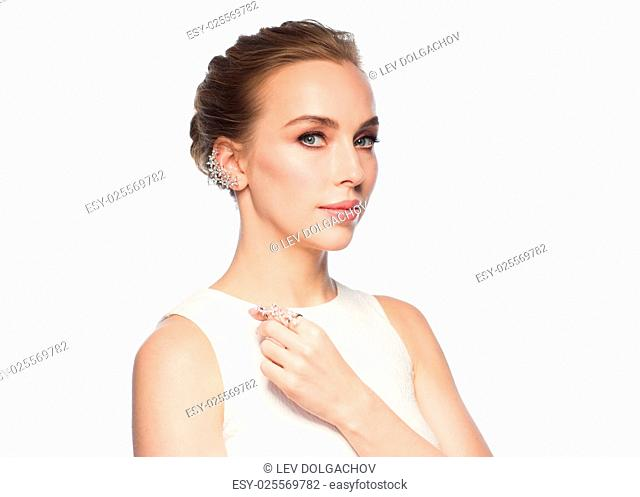 jewelry, luxury, wedding and people concept - smiling woman in white dress with diamond earring and ring over white background