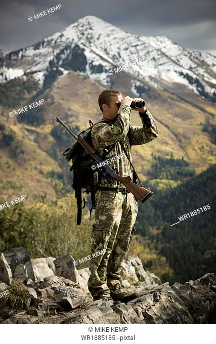 hunter using binoculars to spot prey