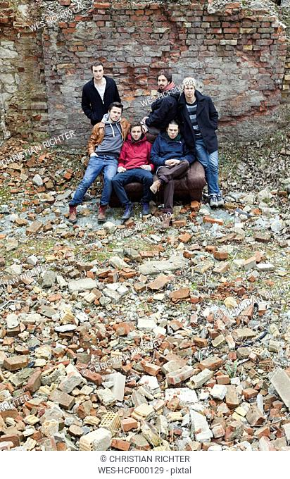 Group picture of six friends surrounded by broken bricks