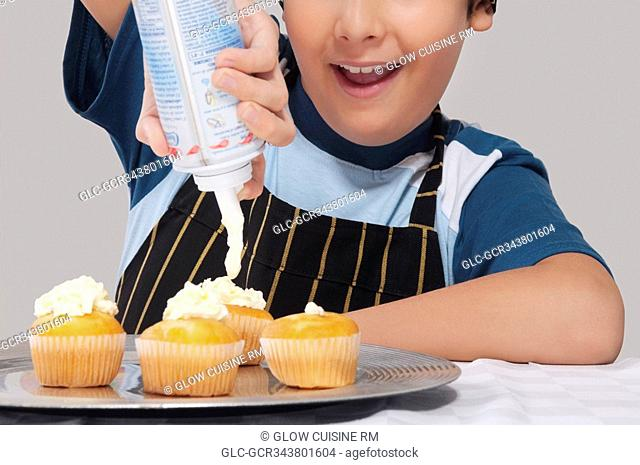 Close-up of a boy putting whipped cream on cupcakes