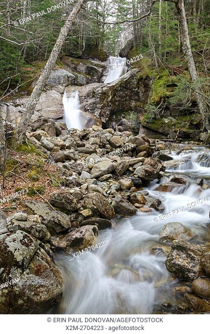 Man sitting in front of Lafayette Brook Falls in the New Hampshire White Mountains USA during the spring months. This waterfall is located along Lafayette Brook...