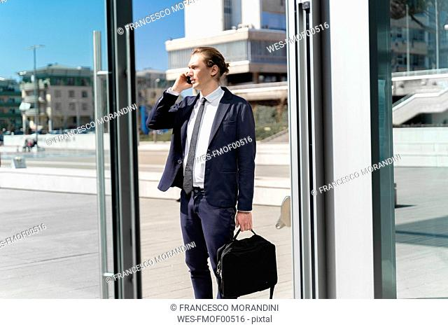 Italy, Florence, young businessman on smartphone outdoor
