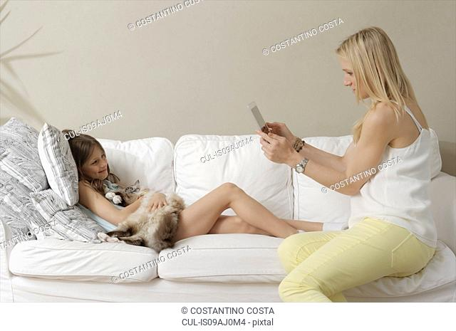 Mother photographing daughter and cat on sofa