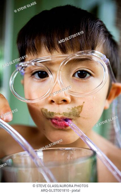 A 6 year old Japanese American boy drinks greens from his weird straw glasses