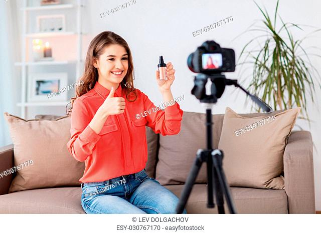 blogging, technology, videoblog, makeup and people concept - happy smiling woman or beauty blogger with foundation and camera recording tutorial video at home...