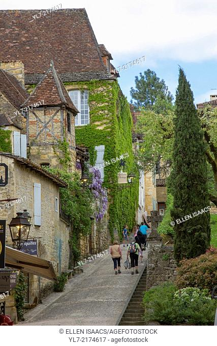 Tourists walk up charming narrow cobblestone sloped street lined with shops in Sarlat, Dordogne region of France