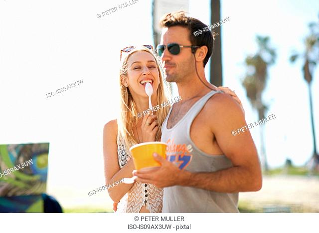 Couple strolling and eating frozen yoghurt at Venice Beach, California, USA