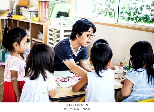 Male teacher talking to group of children at a table n a Japanese preschool