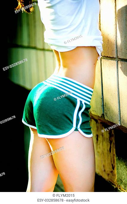 Sexy woman body in green shorts. The model is back. Great ass