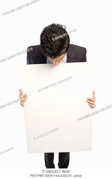 Close-up of a businessman holding a blank placard