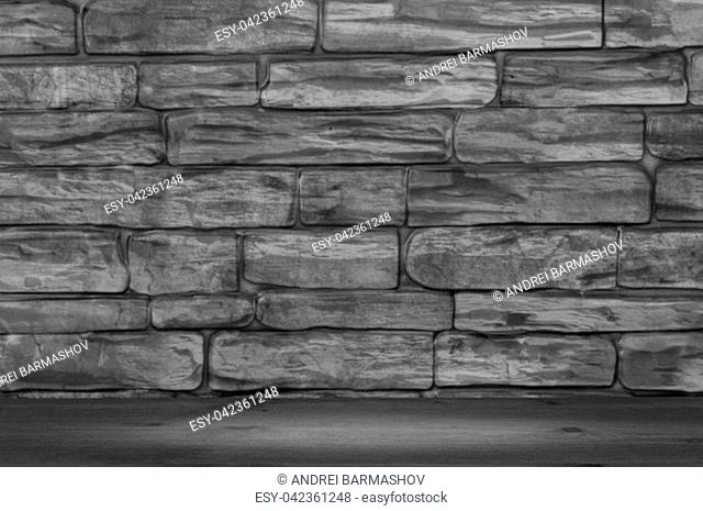 The wall is made of large bricks of black and white color and wooden boards with a spot of illumination
