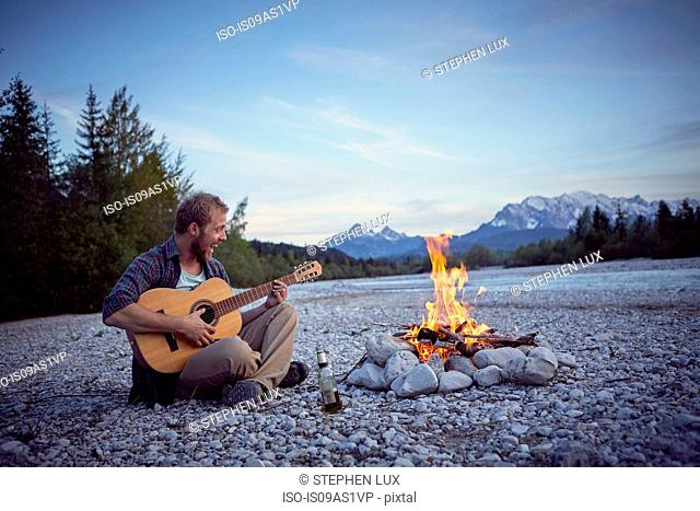 Young man sitting by campfire playing guitar, singing, Wallgau, Bavaria, Germany