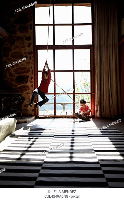 Two siblings in sitting room, brother on rope swing and sister reading