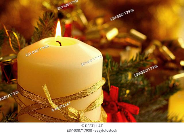 Christmas decorative burning candle, fir branch and decor over golden bokeh background