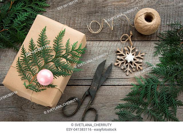 Preparation for Christmas holiday. Christmas Still life of giftbox, decor, twine, fir tree, twigs, vintage scissors. Top view and copyspace. Flat lay