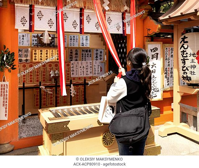 Young Japanese woman pulling a rope to ring the bell at Jishu-Jinja matchmaking shrine, shrine to the god of marriage, at Kiyomizu-dera Buddhist temple in...