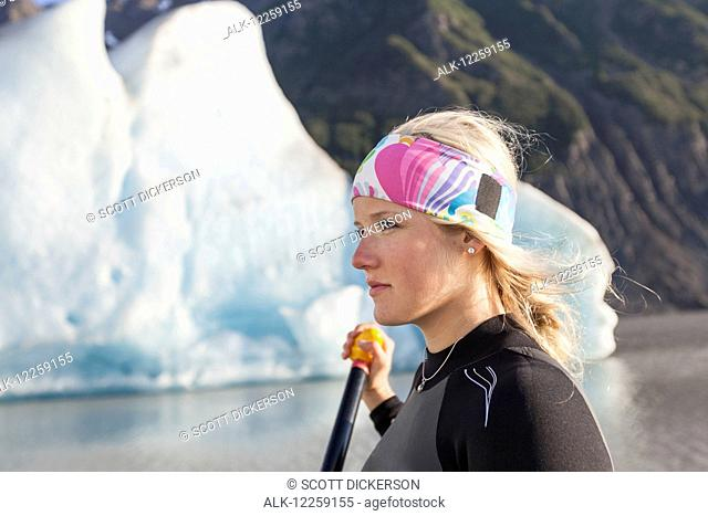 Close up woman paddleboarding near Grewingk glacier in Kachemak Bay State Park, Southcentral Alaska