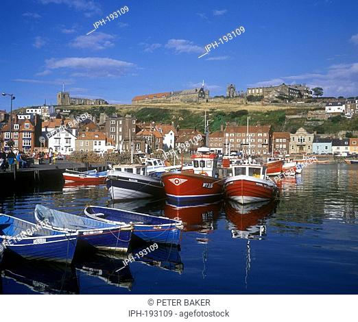 Reflections in the fishing harbour, overlooked by St Mary's Church in the east coast resort of Whitby