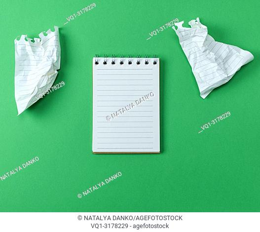 open small blank notebook with white sheets on a green background, next to two crumpled sheets