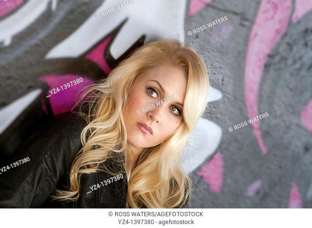 A young woman leaning against a wall covered with graffiti