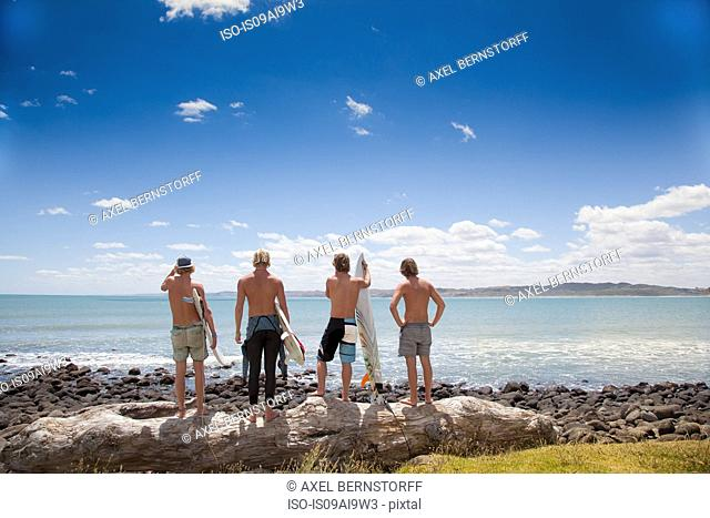Four young male surfer friends watching sea from rocks