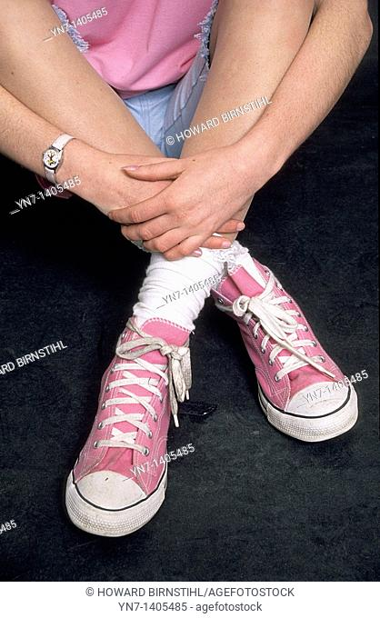 Studio image of a teenage girl's crossed legs with an emphasis on her pink and white trainers