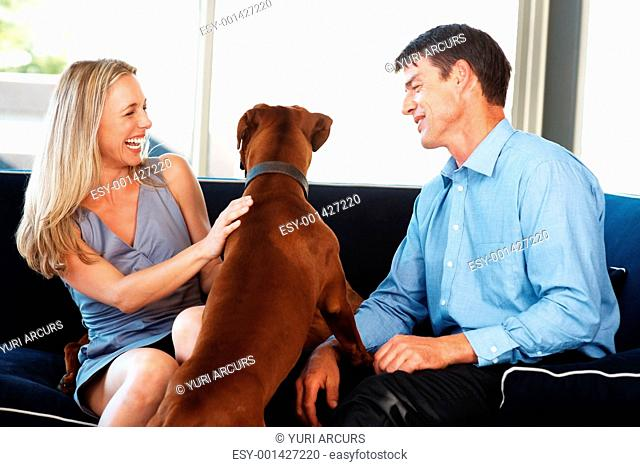 Portrait of a cute young couple having fun with their pet dog at home - Indoor