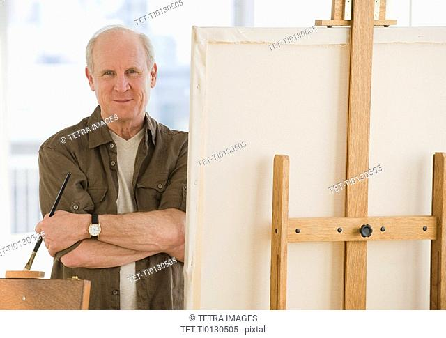 Senior man standing next to easel