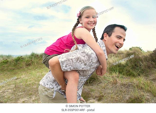Father carrying daughter piggy back