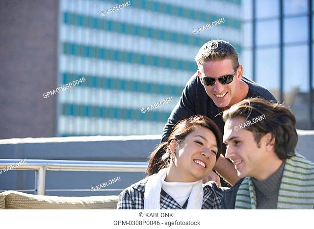 Portrait of multi-ethnic friends relaxing on rooftop of downtown condo in city