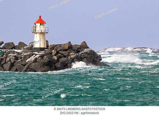 Lighthouse on a pier with a stormy ocean and big waves, Andenes, Norway