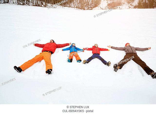 Parents and sons lying in snow covered landscape, Elmau, Bavaria, Germany