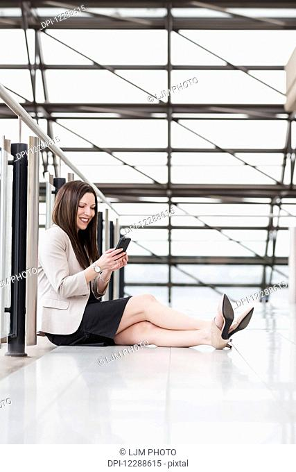 Mature business woman sitting down during a break and texting on her smart phone; Edmonton, Alberta, Canada