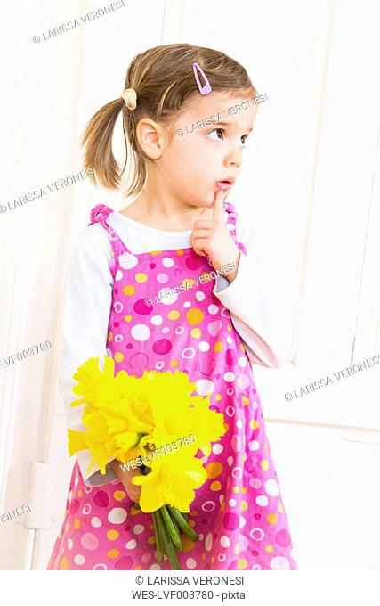 Portrait of little girl with bunch of daffodils