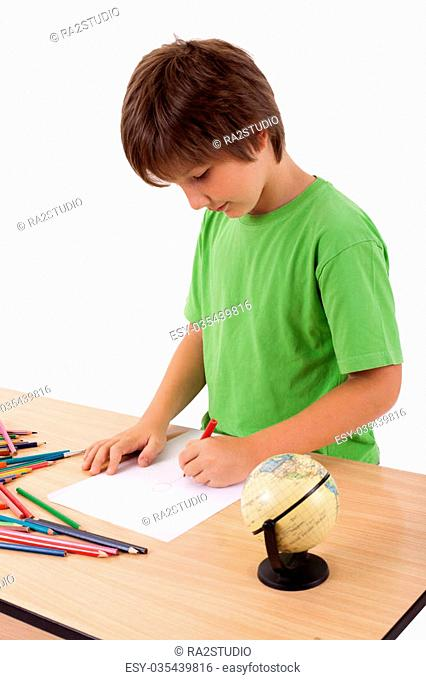 Young boy near table drawing with color pencils