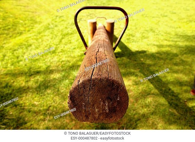 old wooden balance teeter totter in the park, grass background