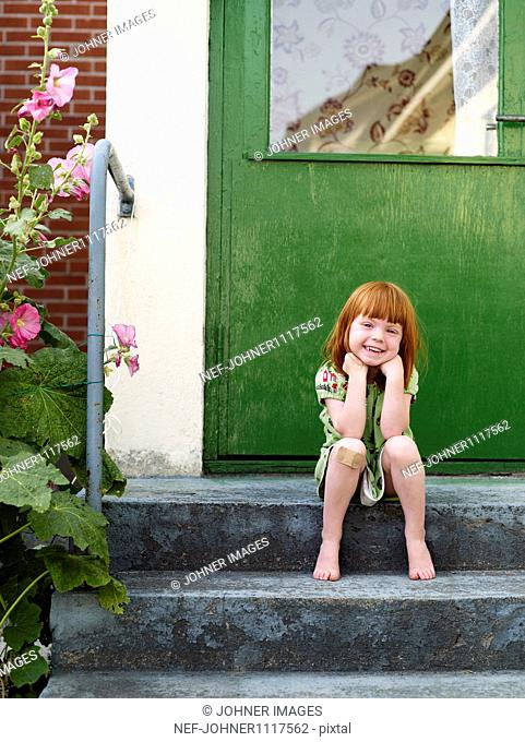 Girl sitting on step in front of door